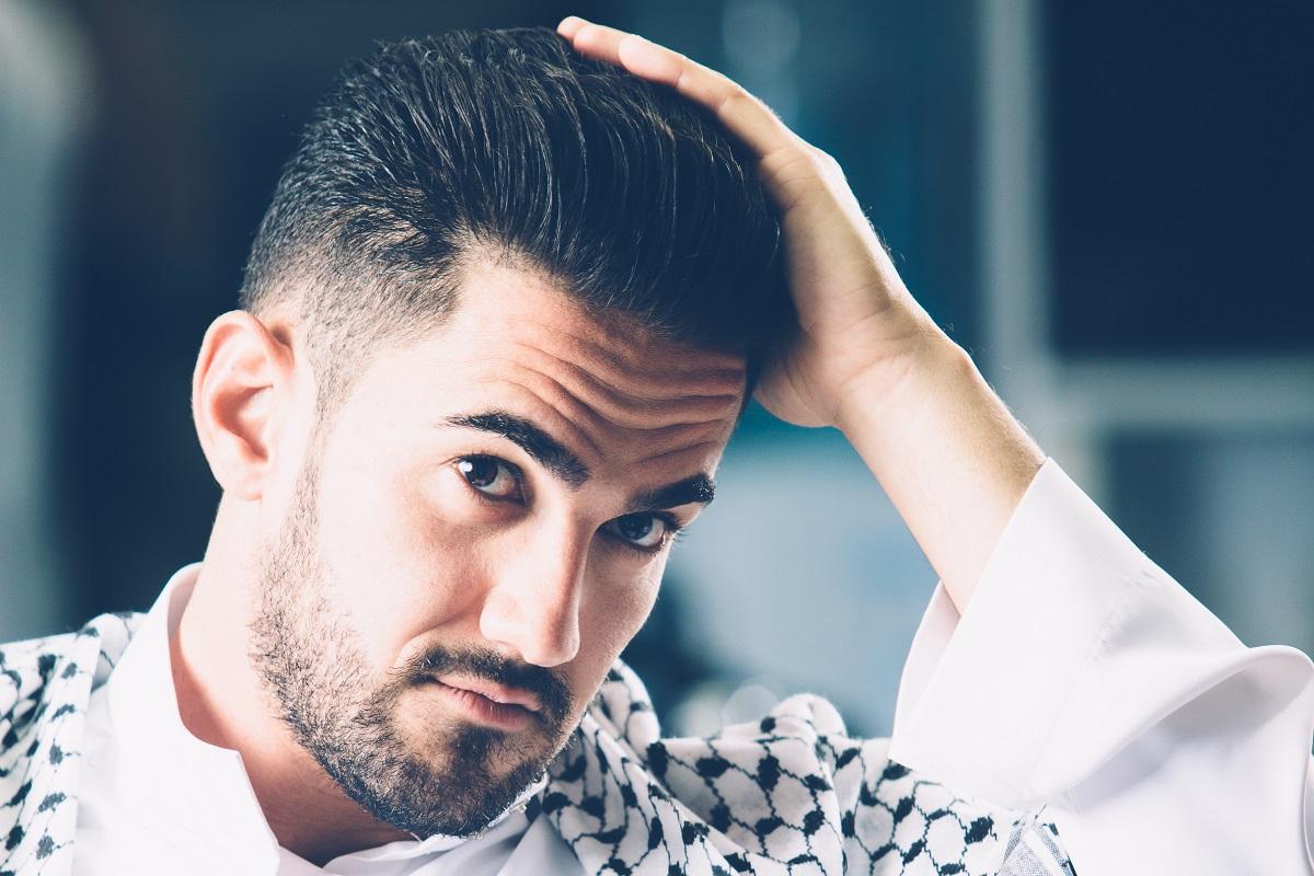 homem conferindo o crescimento do cabelo