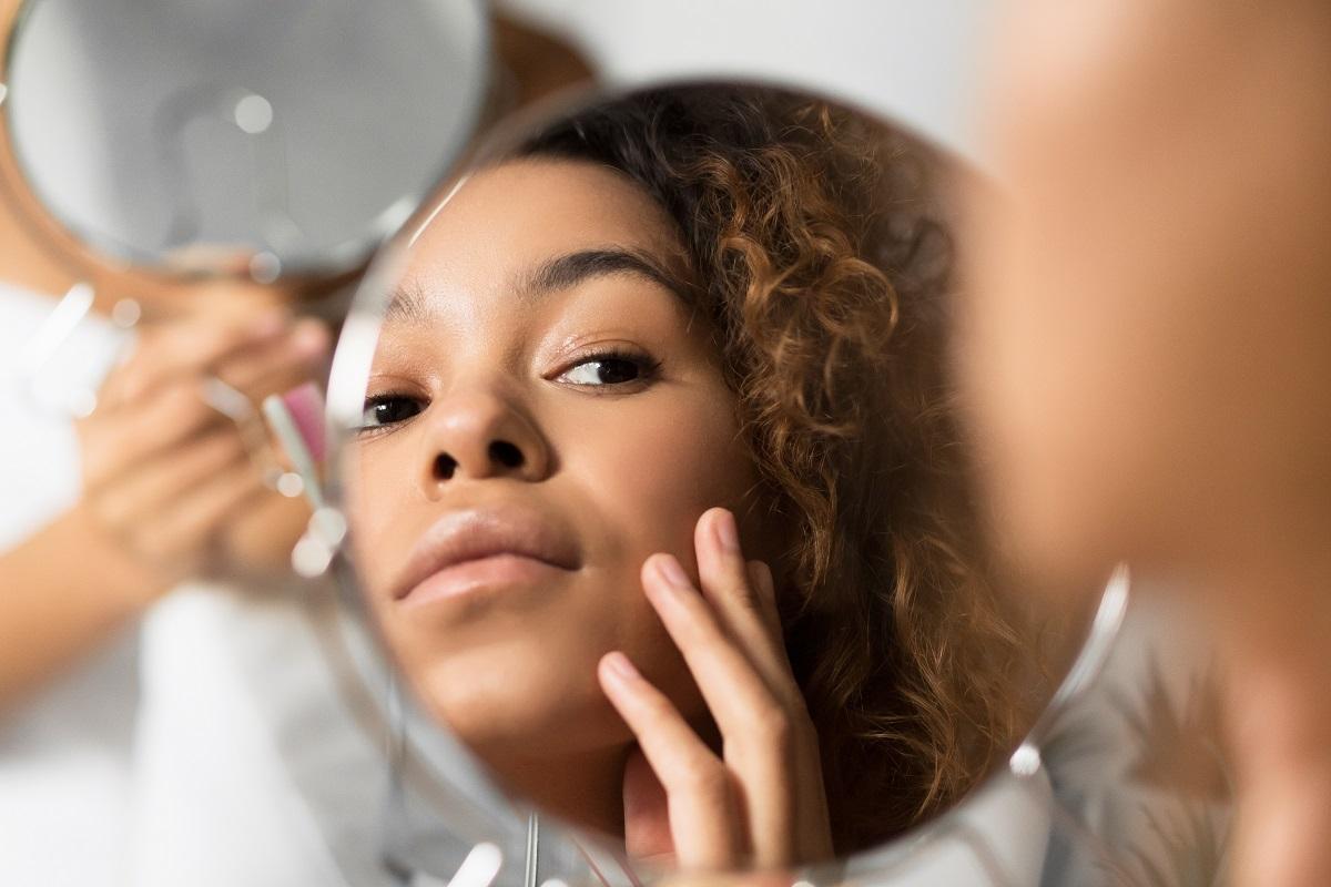 mulher procurando manchas na pele